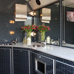 The interior of a luxury toilet trailer with a vase of stunning spring tulips supplied by Barny Lee Marquees for weddings and events