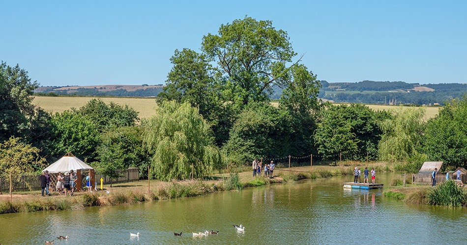 A lake in Somerset with a raft and ducks and children playing at a marquee garden party