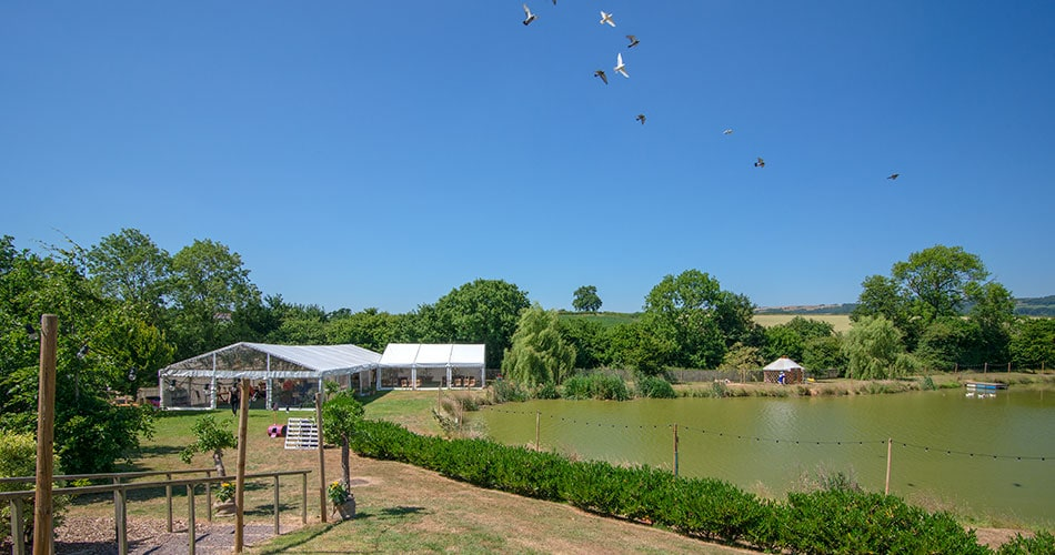A beautiful marquee by a lake in mid summer with doves fling overhead
