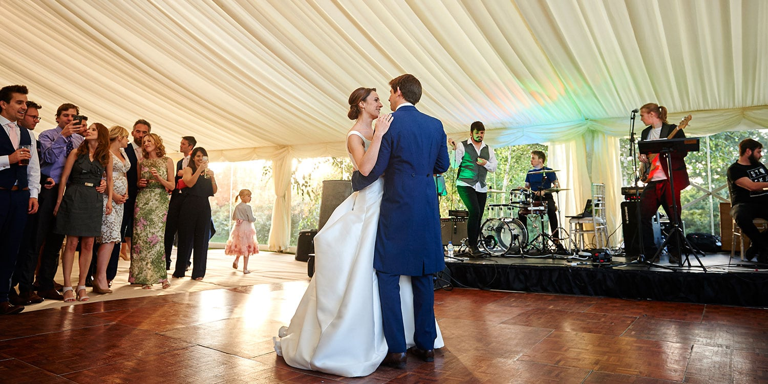 A happy couple enjoy their first dance in front of friends on one of Barny Lee's dance floors.