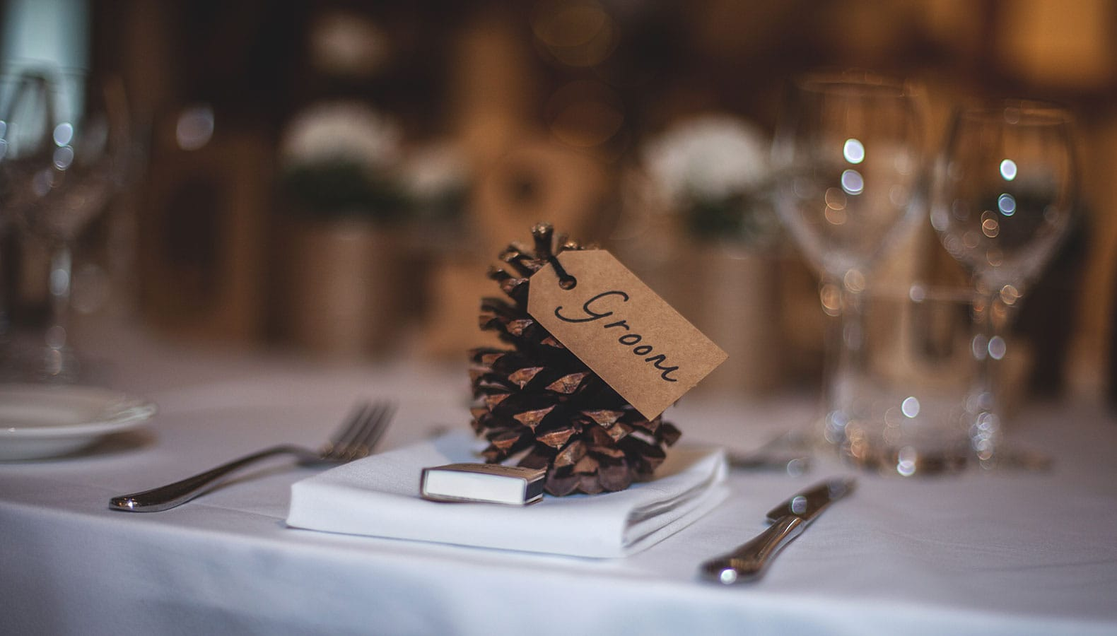 Pine cone table setting name place holder at a wedding in a marquee - ideas for affordable marquee decoration